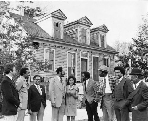 Group of preservatists standing in front of the Mann-Simons Cottage.